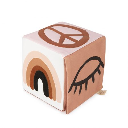 Handmade organic cotton sensory activity cube in neutral colours, showing a rainbow, peace sign and closed eye on a white background