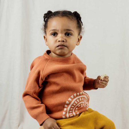 Baby wearing rainbow jumper